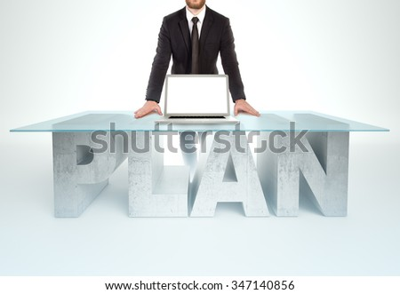 Confident business man leaning on PLAN table with open laptop Bussines concept - stock photo