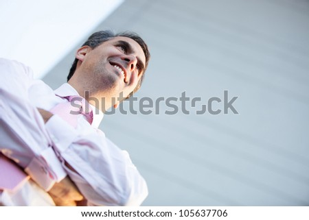 Confident business man lwith arms crossed and smiling - stock photo