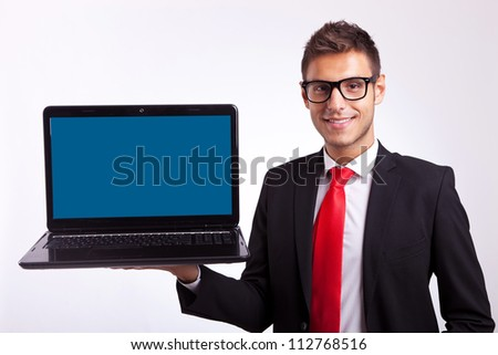 Confident business man or student in glasses holding a laptop - stock photo