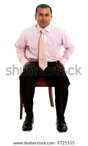 confident business man sitting on a chair isolated over a white background