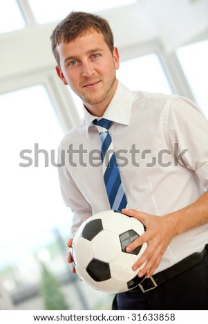 Confident business man standing with a football at an office - stock photo