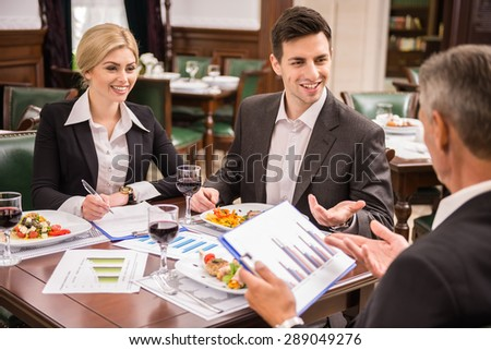 Confident business partners in suits discussing contract during business lunch. - stock photo