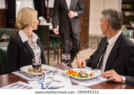 Confident business partners meet at business lunch in cafe. - stock photo