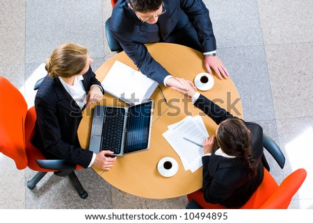 Confident business partners sitting at the table and shaking hands - stock photo