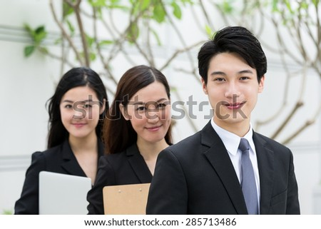 Confident business people queue up together - stock photo