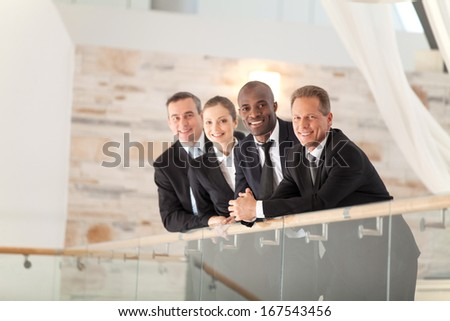 Confident business team. Low angle view of four confident business people standing close to each other and smiling at camera - stock photo