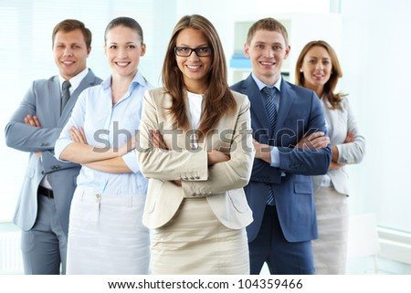 Confident business team with a female leader looking at camera and smiling - stock photo