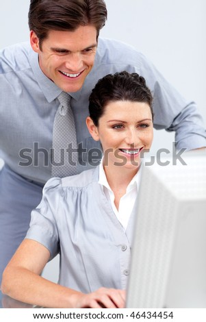 Confident business woman and her colleague working at a computer in the office