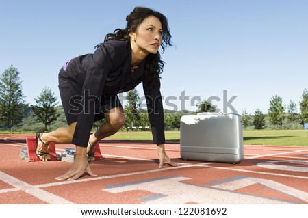 Confident business woman at start position of a racing track with briefcase against sky - stock photo