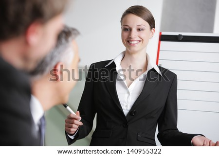 Confident business woman giving a presentation on whiteboard - stock photo