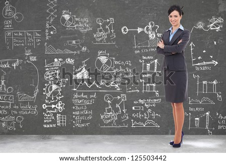 confident business woman in front of lots of graphs and diagrams from a big plan or presentation - stock photo