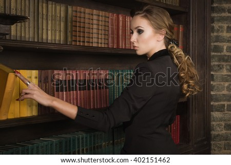 Confident business woman in the classical library room. Low key. No intellectual content