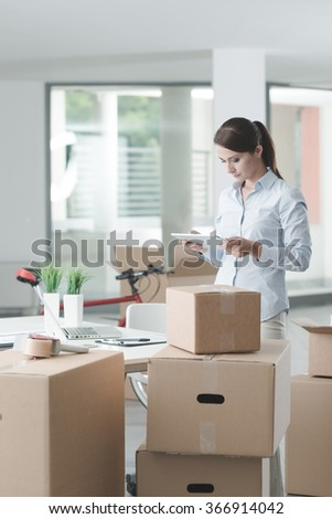 Confident business woman moving in her new office and using a digital tablet, she is surrounded by cardboard boxes - stock photo