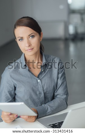 Confident business woman sitting at office desk and using a touch screen digital tablet, she is smiling at camera