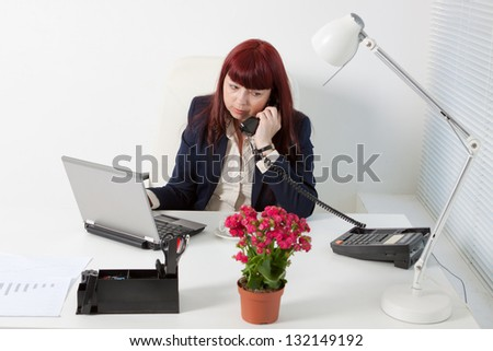 Confident business woman speaks by phone  in a comfortable modern office - stock photo