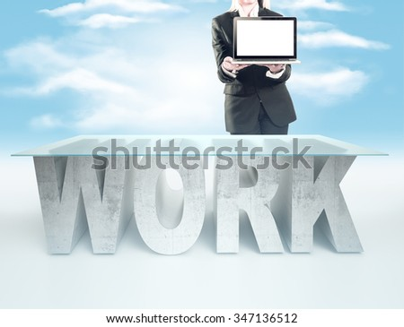 Confident business woman, standing near the WORK table and holding a laptop - stock photo