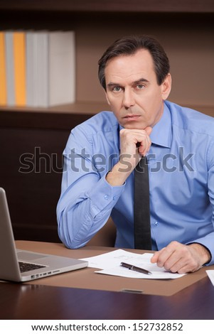 Confident businessman. Confident mature businessman sitting at his working place and holding his hand on chin