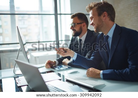 Confident businessman consulting his colleague and pointing at computer monitor at meeting - stock photo