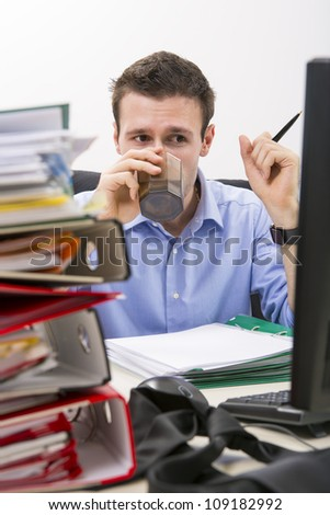 Confident businessman doing paperwork in front of his computer, drinking water, surrounded by huge piles of documents. - stock photo