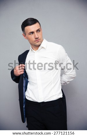 Confident businessman dressing jacket over gray background and looking away - stock photo