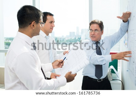Confident businessman explaining sketch to his colleagues at meeting - stock photo