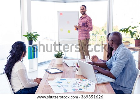 Confident businessman giving presentation in creative office - stock photo