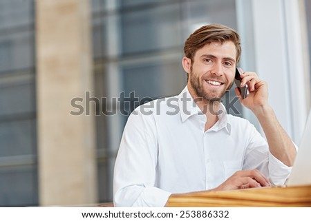 Confident businessman holding his mobile phone and smiling at the camera - stock photo
