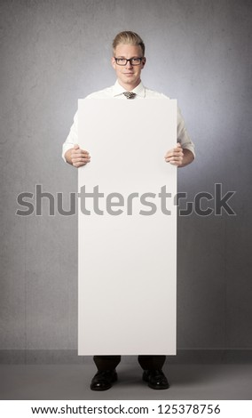 Confident businessman holding white empty vertical panel with space for text isolated on grey background. - stock photo