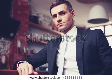 Confident businessman in formal cloths resting in the kitchen - stock photo