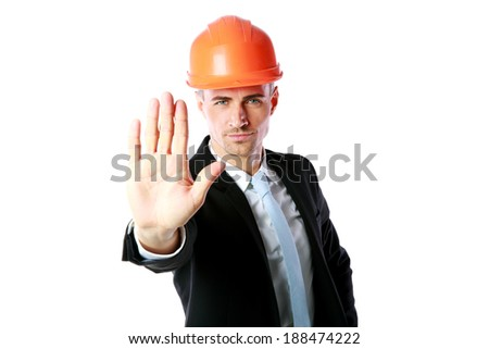 Confident businessman in helmet showing stop gesture over white background - stock photo