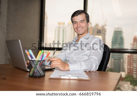 Confident businessman in office with blur business people working background.Work space concept.