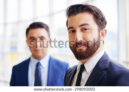 Confident businessman looking at camera on background of his colleague - stock photo