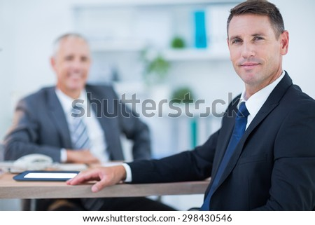 Confident businessman looking at camera with colleague behind in the office - stock photo