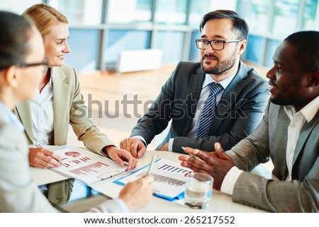 Confident businessman looking at his colleagues at meeting - stock photo