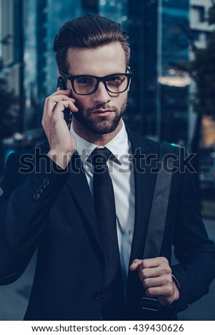 Confident businessman on the phone. Night time image of confident young man in full suit talking on the mobile phone and looking at camera while standing outdoors with cityscape in the background - stock photo