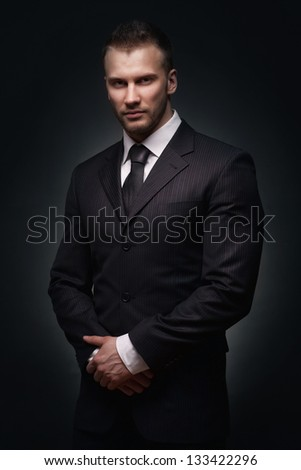 Confident businessman portrait isolated on dark background - stock photo