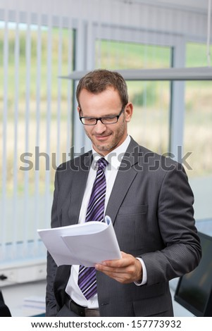 Confident businessman reading a document standing in his office with a satisfied smile - stock photo