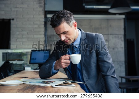 Confident businessman reading magazine and drinking coffee in cafe - stock photo