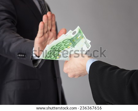 Confident businessman rejecting an offer of money on grey background - stock photo
