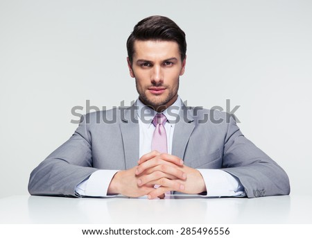 Confident businessman sitting at the table over gray background and looking at camera - stock photo