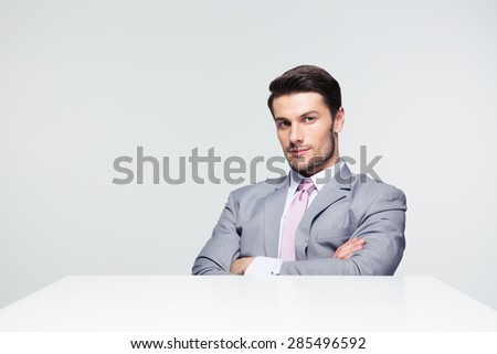 Confident businessman sitting at the table with arms folded over gray background. Looking at camera - stock photo