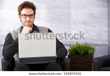 Confident businessman sitting in office lobby, working on laptop, smiling. - stock photo