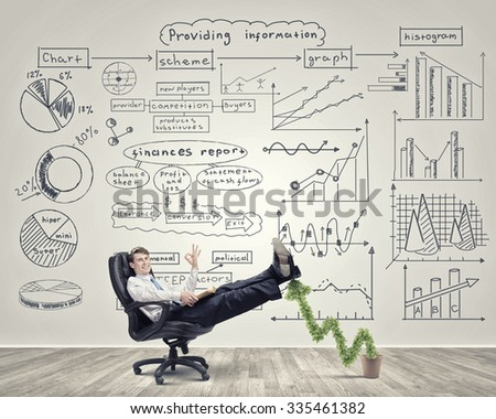 Confident businessman sitting on chair with legs up and showing ok gesture - stock photo