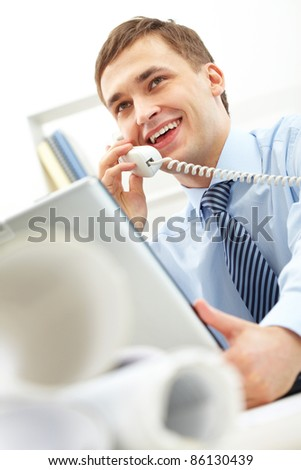 Confident businessman speaking on the telephone in office - stock photo