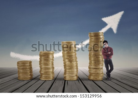 Confident businessman standing next to gold coins chart with blue sky background