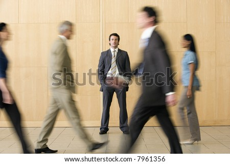 Confident businessman standing whilst busy colleagues walk past - stock photo