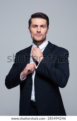 Confident businessman straightening his tie over gray background and looking at camera - stock photo