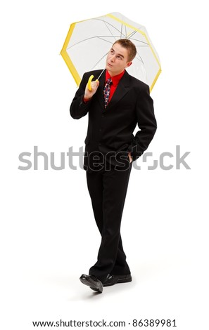 Confident businessman walking and holding umbrella above his head - stock photo