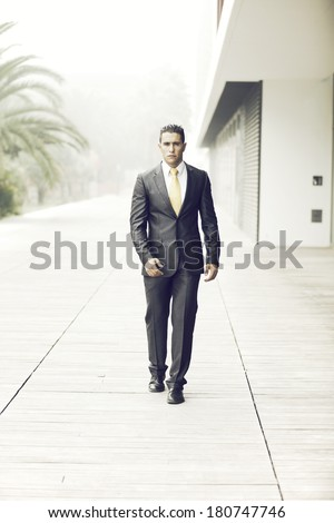 Confident businessman walking next to his office building - stock photo