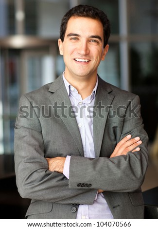 Confident businessman with arms crossed at the office - stock photo